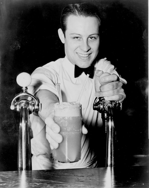 1950s diner worker smiling as he pours carbonated beverage for soda fountain customer