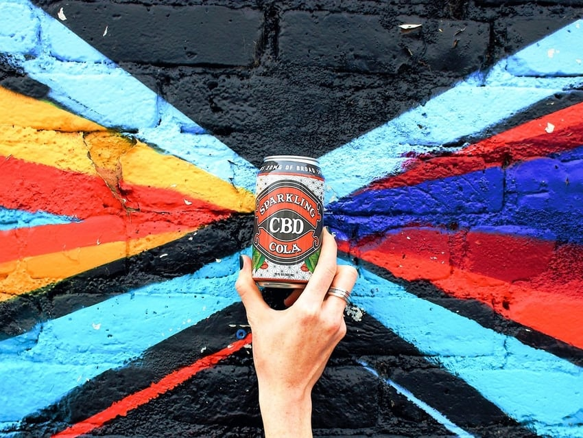 Can of Sparkling CBD Cola Raised Next to Colorful Painted Background
