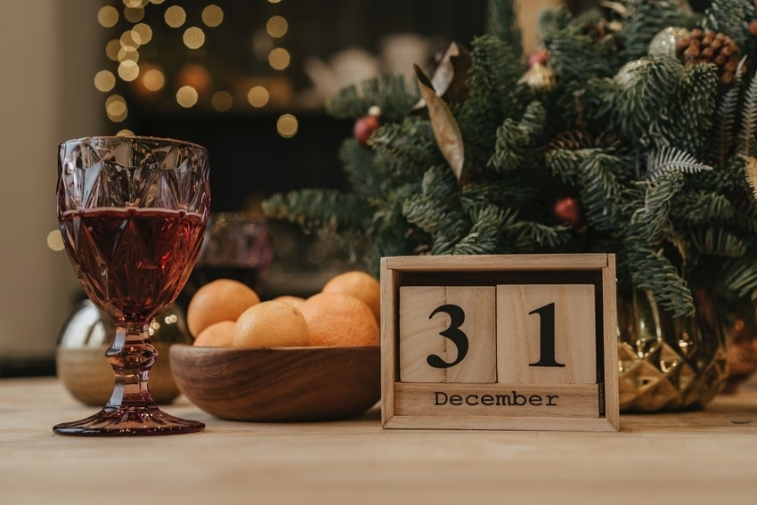 Glass of Sparkling CBD Sangria beside bowl of citrus fruit, Christmas tree and wooden date counter showing