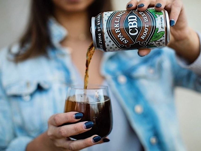 Woman in denim jacket pours Sparkling CBD Root Beer into drinking glass for cocktail