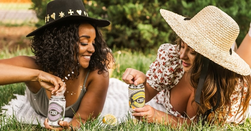 Smiling women on outdoor picnic blanket with cans of Sparkling CBD Lemonade and Sparkling CBD Black Cherry Soda
